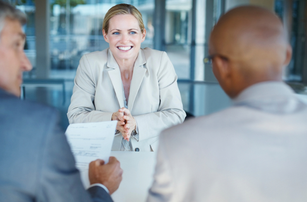 Smiling business woman sitting in front of panel of interviewers